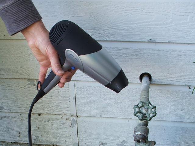 گرم کردن لوله با سشوار برای آب کردن یخ زدگی